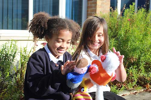 Homepage Westbury CofE Junior School children looking at handmade puppets on bench outside