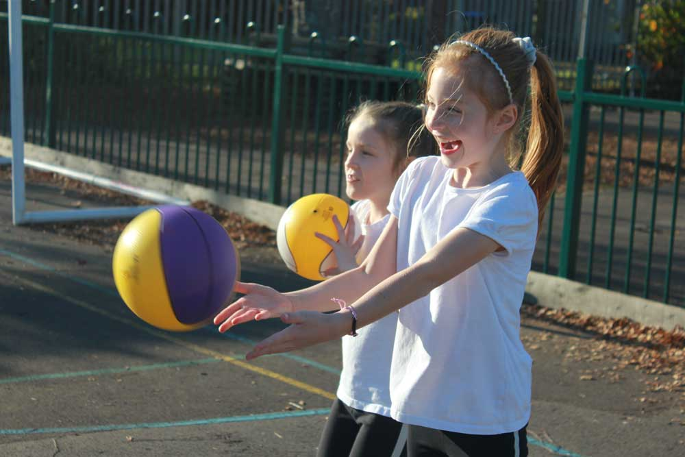 Sports Premium Image - Girls playing netball.