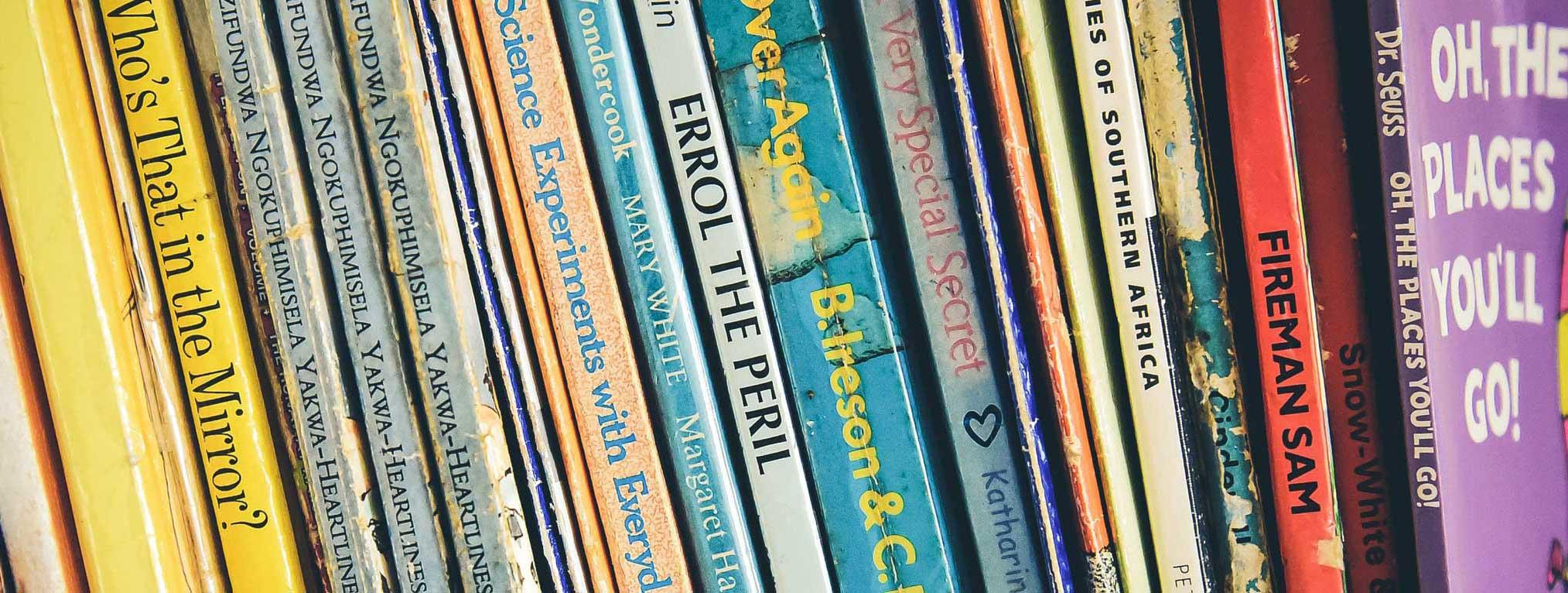 wjs staff hero image. A row of children's books on bookshelf
